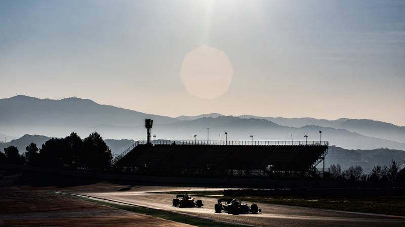 Mountains in the background of the Circuit de Catalunya as two F1 cars drive past during 2020 preseason testing