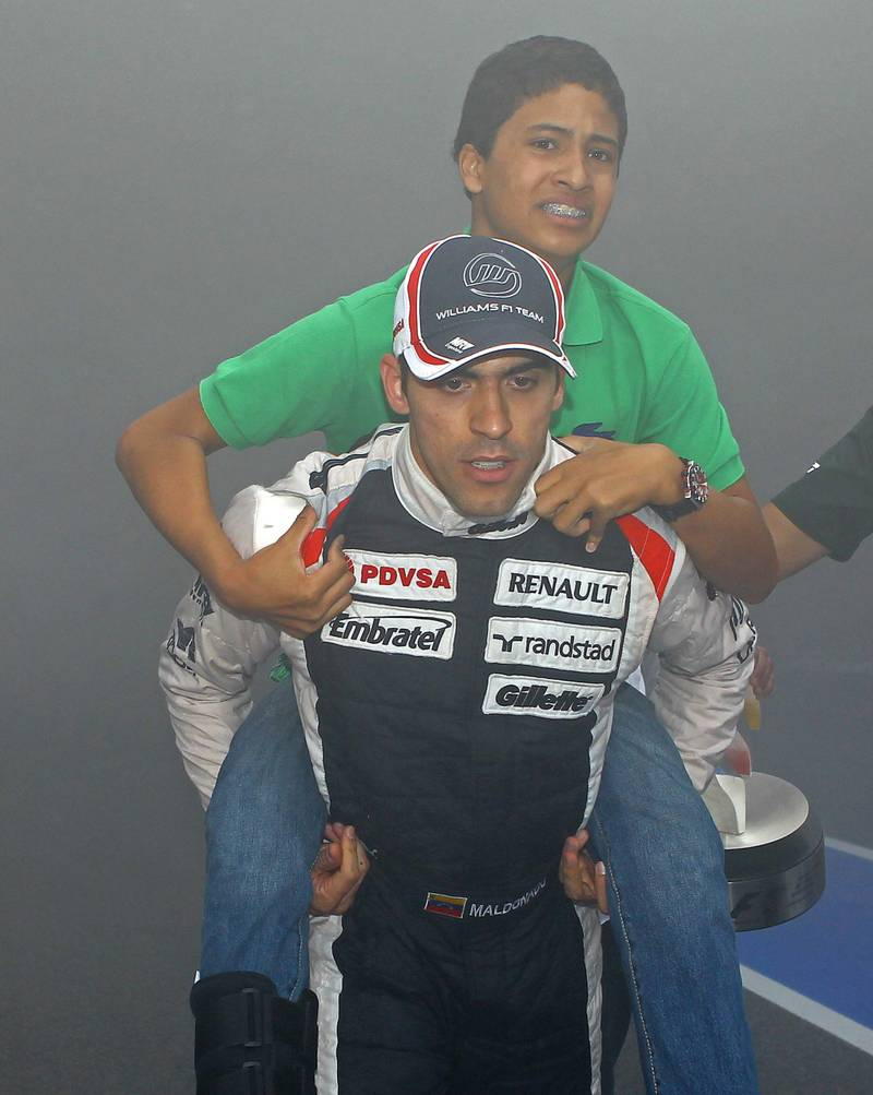 Pastor-Maldonado-carries-his-nephew-away-from-the-Williams-garage-fire-at-the-end-of-the-2012-Spanish-Grand-Prix