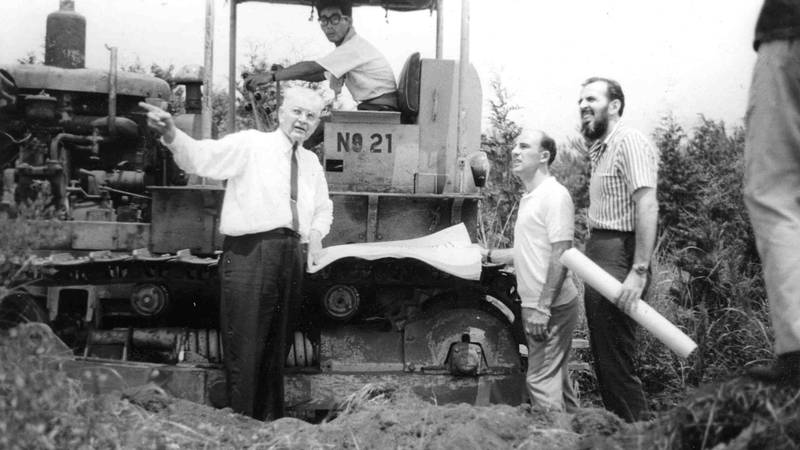 Stirling Moss and Don Nichols next to a tractor at the proposed site of the Fuji Speedway