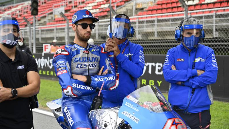 Alex Rins surrounded by team mechanics in protective visors ahead of the 2020 MotoGP Catalan Grand Prix