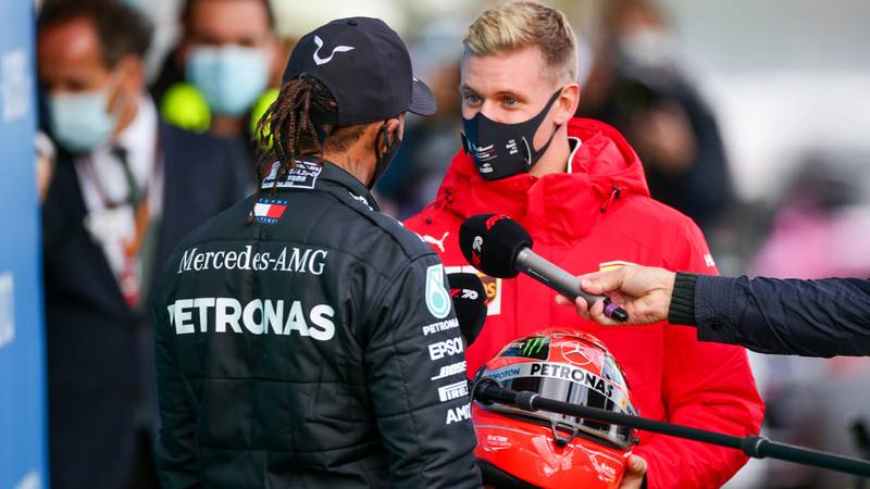 Mick Schumacher presents Lewis Hamilton with one of his father's helmets after the 2020 F1 Eifel Grand Prix at the Nurburgring